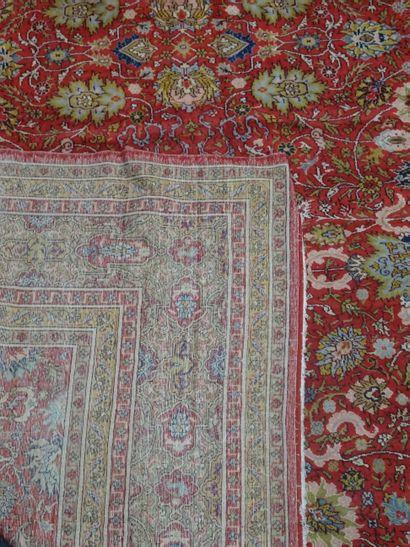 SPARTA  Important tapis à fond rouge à décor...