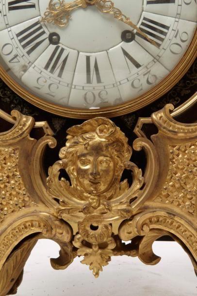 Pendule et une console La pendule de forme galbée en placage d'écaille brune, laiton...