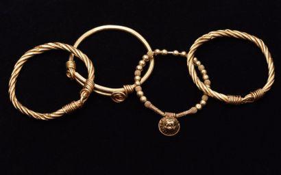 Lot de 4 bracelets jonc en or 18K (750 millièmes), l'un à pans coupés, deux à maille...