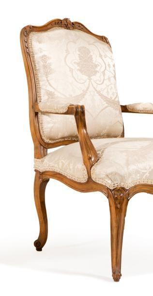Suite de six fauteuils en hêtre mouluré et sculpté à assise évasée et à dossier...