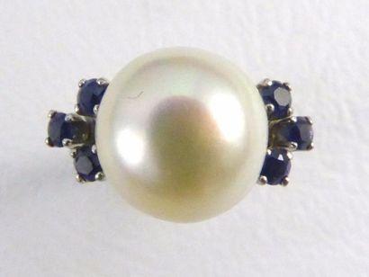 Bague en or gris 18k (750 millièmes) sertie d'une perle blanche épaulée de petits...