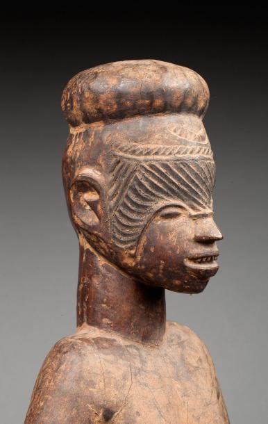 Statue présentant un ancêtre masculin nu debout, la tête surmontée d'un chignon...