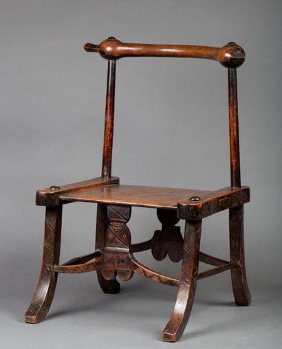 Chaise en bois à décor de symboles incisés...