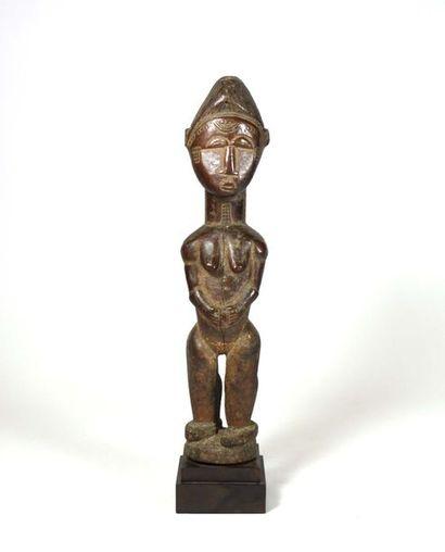 Statuette féminine présentée debout sur un piédestal circulaire. Ses mains sont...