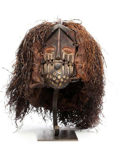Masque de danse accompagné de sa parure d'origine. Il présente un visage aux traits...
