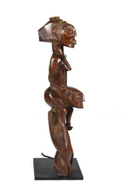 Statuette présentant un personnage transportant une femme sur ses épaules  Il s'agit...