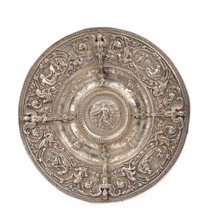 Plat rond d'apparat en argent, l'aile à décor en repoussé de quatre médaillons ornés...