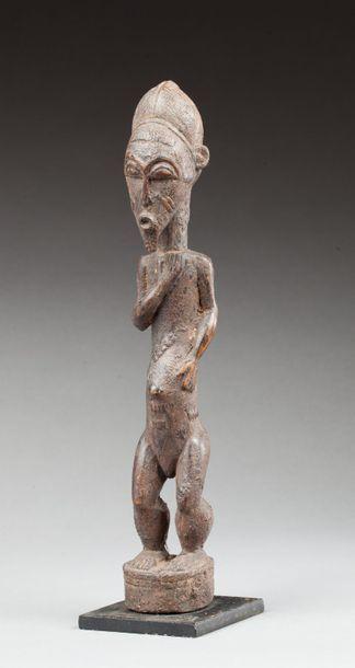 Statuette masculine présentant un personnage sur un piédestal circulaire, une de...
