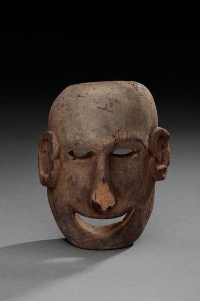 Masque sculpté d'un visage à l'expression...