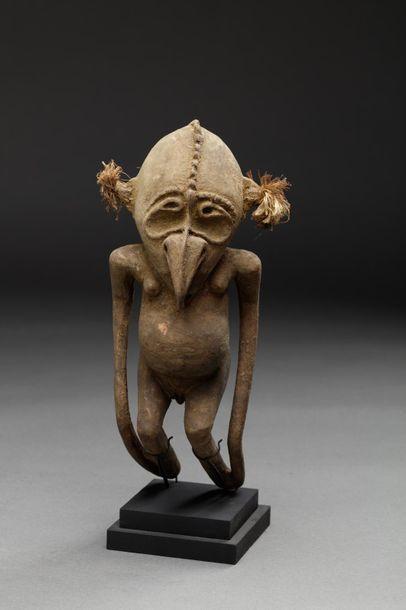 Statuette présentant un personnage accroupi, le nez se transformant en bec d'oiseau....