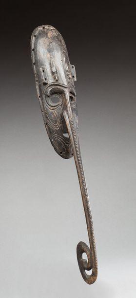 Masque au nez en forme de bec d'oiseau.  Bois patiné.  De style Papouasie-Nouvelle-Guinée....