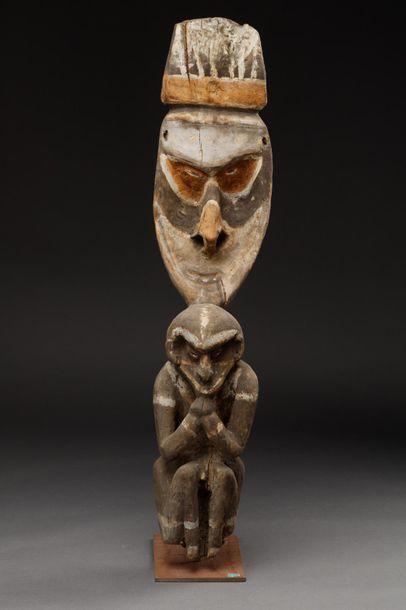Statuette totémique personnage accroupi portant un casque sur la tête.  Région du...