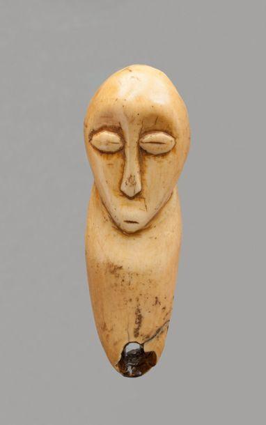 Amulette présentant une tête, les yeux en...