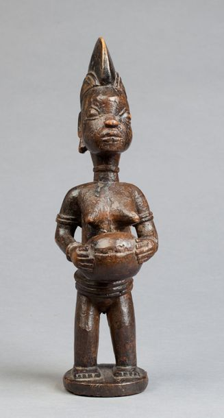 Statue féminine présentée sur un piédestal circulaire. Elle tient dans ses mains,...