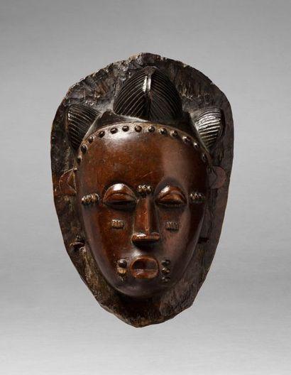 Masque de danse présentant une tête de dignitaire, la coiffe agencée par trois lobes...