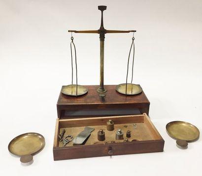 Une balance en bois et laiton avec un tiroir...