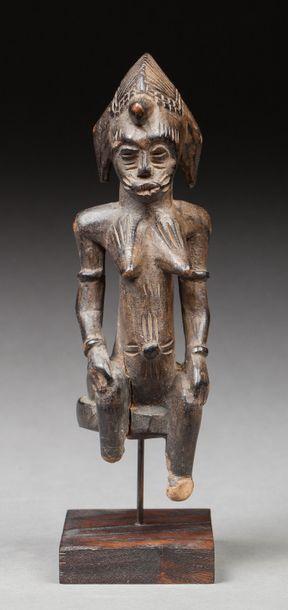 Statuette présentant une jeune fille assise,...