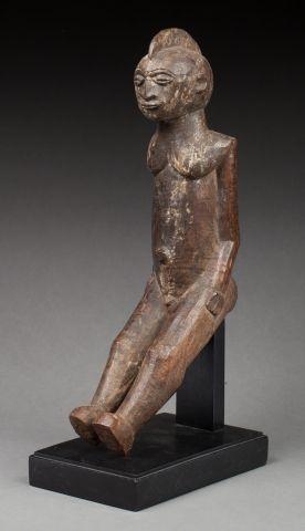 Statuette présentant un jeune homme nu assis....