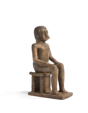 Statue présentant un chef assis sur un piédestal...
