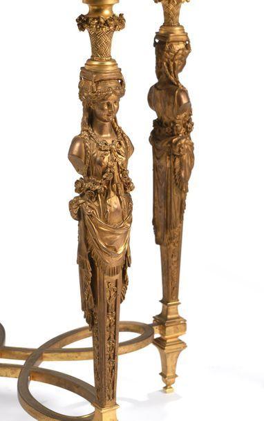 Paire de guéridons de forme ronde, le piétement en bronze ciselé et doré formé par...