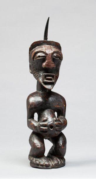 Fétiche ancestral présentant un personnage masculin de proportions puissantes, ses...