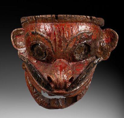 Grand masque de cérémonie présentant un visage avec une bouche démesurée ouverte,...