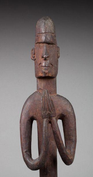 Statue totémique présentant un jeune guerrier debout, les mains jointes dans un...