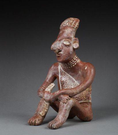 Statuette anthropomorphe présentant un personnage assis tenant un projectile dans...