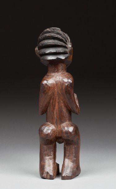 Statuette hermaphrodite présentée debout, les mains posées sous les seins dans un...
