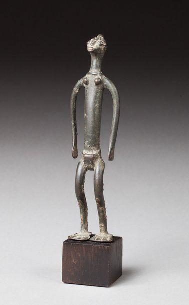 Statuette présentant un personnage aux belles formes longilignes, les jambes légèrement...