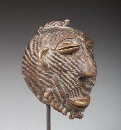 Tête votive, elle présente un visage ancestral à l'expression douce.  Laiton ancienne...