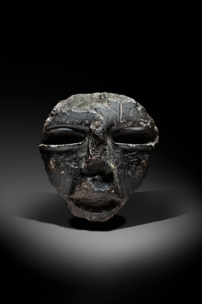 Masque cultuel sculpté d'un visage aux yeux...