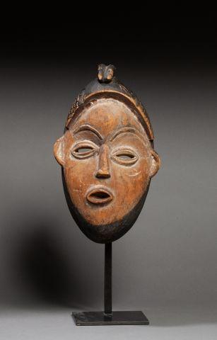 Masque sculpté d'un visage surmonté d'une...