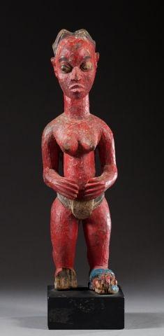 Statuette féminine présentée debout les avant-bras et les mains enveloppant symboliquement...