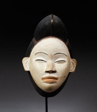 Masque féminin sculpté d'un visage à l'expression...