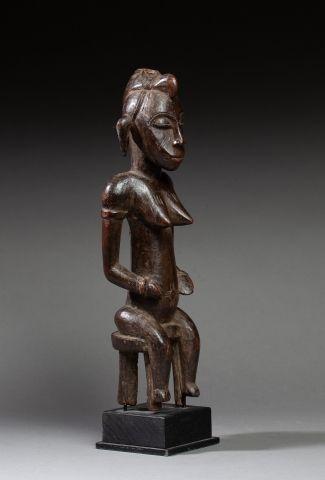 Statuette présentant une jeune femme assise...