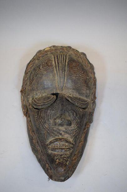 Masque en bois à belle patine brune faisant...