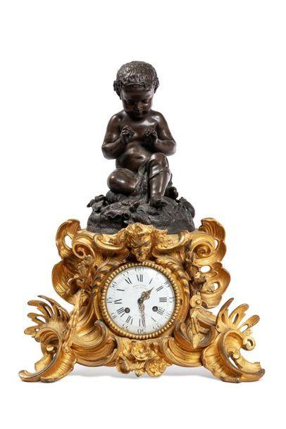 PENDULE A HAUTE BASE de bronze doré formée d'agrafes, coquilles, mascarons et fleurs...