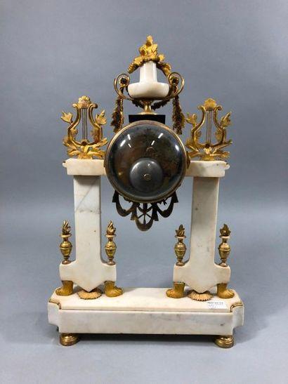 Pendule en marbre blanc et bronze doré de forme portique, le cadran à chiffres arabes,...