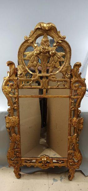 GRAND MIROIR A PARECLOSES en bois sculpté et doré de forme chantournée, les montants...