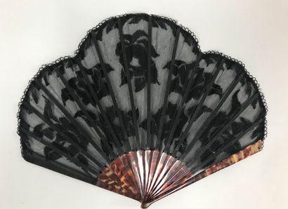 Fleurs noires brodées, vers 1920-1930  Éventail de forme ballon, la feuille en tulle...