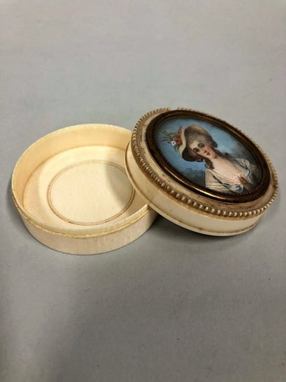 Set of two circular ivory boxes, the lid surmounted by a miniature representing...