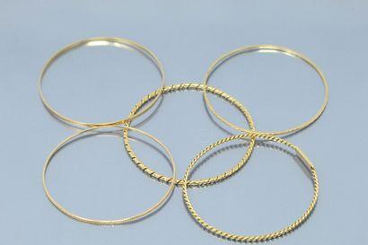 Cinq bracelets joncs en or jaune 18K (750)...