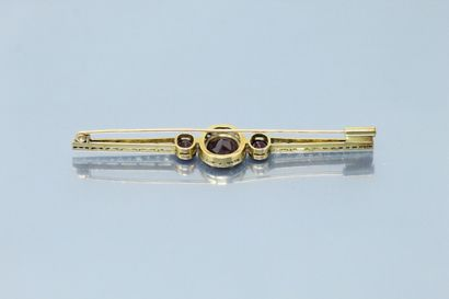 Broche barrette en or jaune 18K (750) et platine centrée d'un grenat pyrope-almandin...
