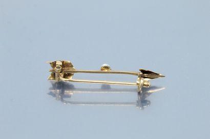 Broche en or jaune 18k (750) en forme de flèche, une perle baroque en son centre....