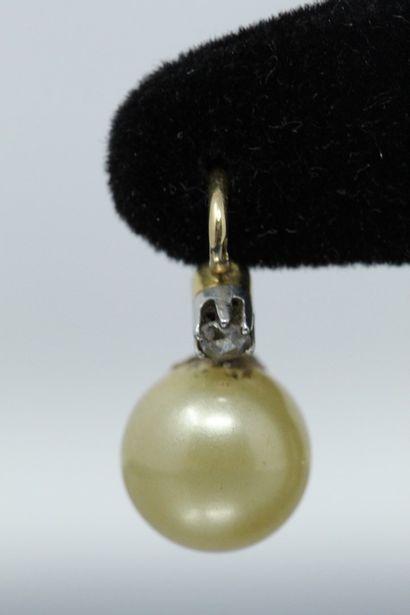 Paire de dormeuses en or jaune 18k (750) une perle baroque sertie, épaulée par un...