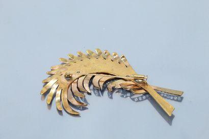 Broche en métal doré en forme de plumes ajourées, l'une d'elles pavée de pierres...