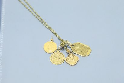 Chaîne en or jaune 18k (750) retenant trois pedentifs en or jaune 18k (750).  On...