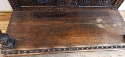 Dressoir en bois naturel sculpté en partie basse d'un décor de rinceaux, vase fleuri,...