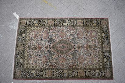 Silk carpet on a white background, the borders on a black background. H: 155 cm...
